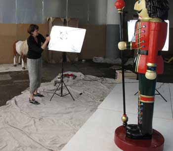 Claire in our photography studio, setting up lighting while watched over by the Nutcracker King with Scepter. soon to have his picture taken.